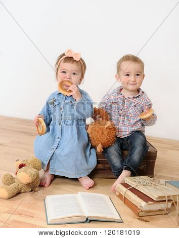Little Girl And Boy Sitting On Suitcase Near Book