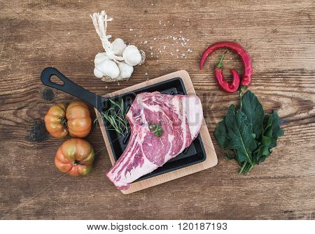 Raw fresh meat ribeye steak with pepper, salt, chili, garlic, spinach, heirloom tomatoes and rosemar