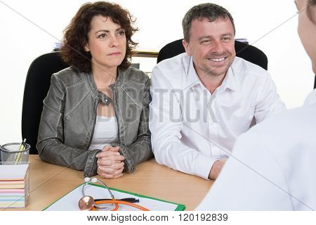 Couple In Discussion With Doctor In Ivf Clinic Sitting At Desk