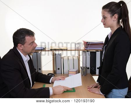 Mid Aged Businessman Blaming Female Employee At Desk In Office