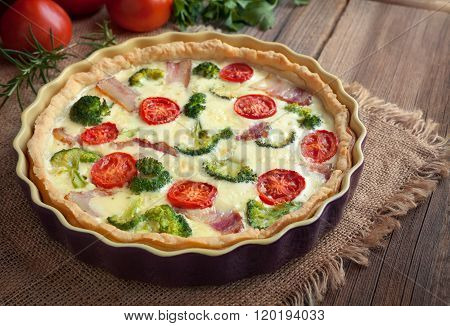 Quiche lorraine tart pie with broccoli, bacon, cheese and tomatoes