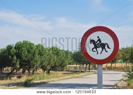 Close-up of round road sign with horse and rider on white background in park area