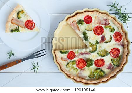 Sliced classic quiche lorraine pie with broccoli, cheese and tomatoes