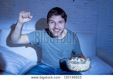young happy fun sitting at living room couch watching sport match on tv cheering his team gesturing victory fist smiling excited holding popcorn in broadcast television concept