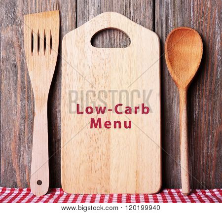Cutting board with text Low-Carb Menu on wooden planks background