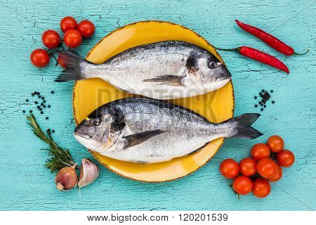 Two Fresh Dorado Fish On Yellow Plate And Vegetables On Blue Table. Top View.