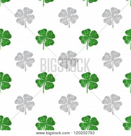 Seamless pattern of abstract four-leaf clovers of green and silver glitter
