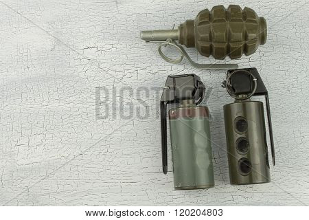 Hand grenade on shadowed, cracked background. War game