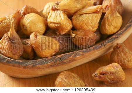 bowl of sun dried figs on wooden table - close up