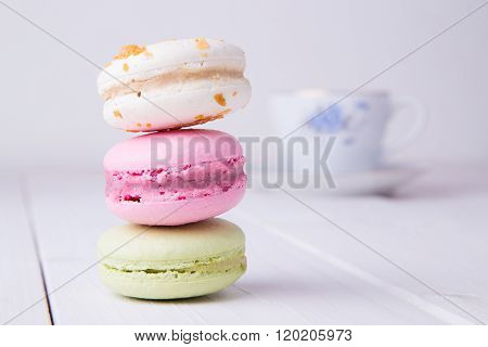 Colorful macaroons vertically stacked with cup of tea