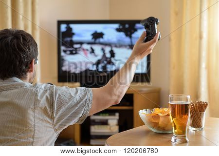 Man Playing War Video Game On Console In Home - Stock Photo