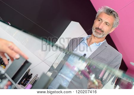 Male customer behind glass counter