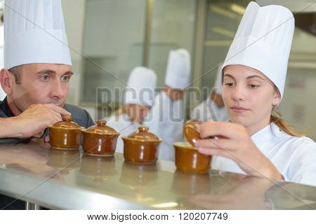 Two chefs looking in ramekin pots