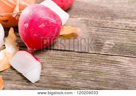 Garden Radish And The Crude Onions Against From Gray Old Boards