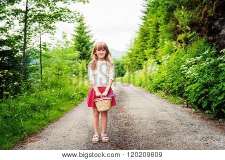 Adorable kid girl of 6-7 years old hiking in forest