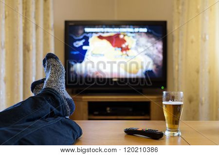 Man Watching Tv (war News) With Feet On Table