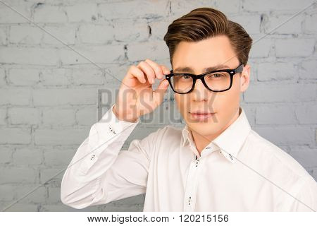 Attractive Young Man In White Shirt Touching His Glasses