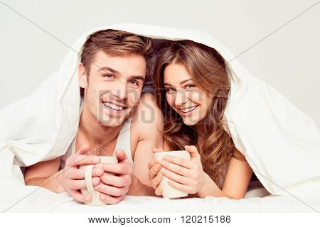 Cheerful Smiling Couple In Love Lying Under Blanket With Coffee And Basking