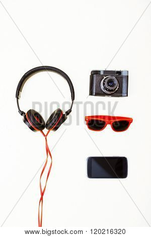 pleasure accessories background headphones, old camera, smart phone and sunglasses