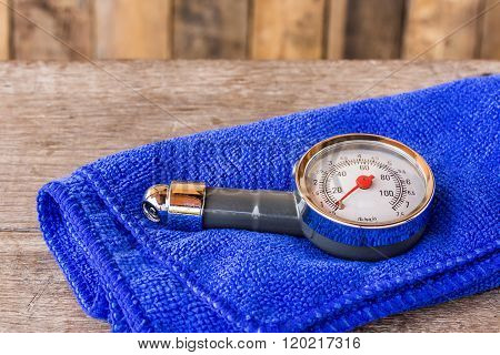 Tire Pressure Gauge And Microfiber Cloth On Wooden Table