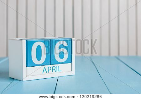 April 6th. Image of april 6 wooden color calendar on white background.  Spring day, empty space for