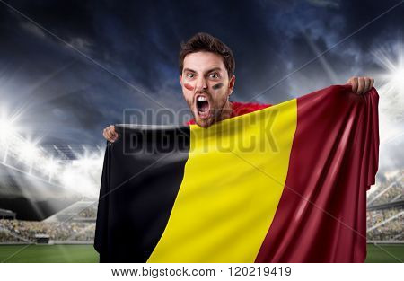 Fan holding the flag of Belgian in the stadium