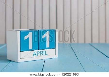 April 11th. Image of april 11 wooden color calendar on white background.  Spring day, empty space fo