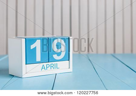 April 19th. Image of april 19 wooden color calendar on white background.  Spring day, empty space fo