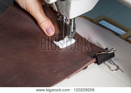 The woman Hand on sewing machine. leather embroidery.