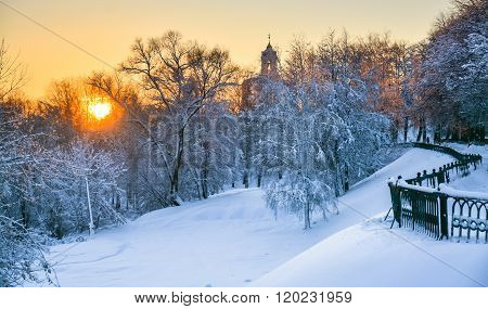 Belfry Of The Monastery And The Snowy Forest At Sunset