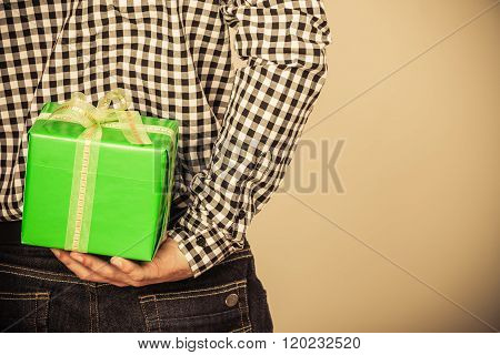 Man Hiding Gift Box Behind Back. Holiday Surprise.