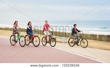 Ordinary family riding bicycles together on the promenade