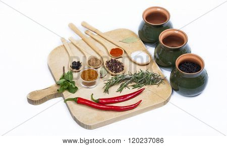 Various colorful spices on kitchen spoons over grunge wooden skulk