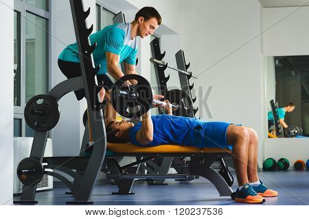 Young Man In Gym Exercising Chest On The Bench Press with barbell