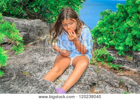 Child girl sitting and eating her lunch after long hiking on the cliff