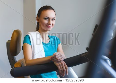 Woman girl resting at the gym on a cross trainer