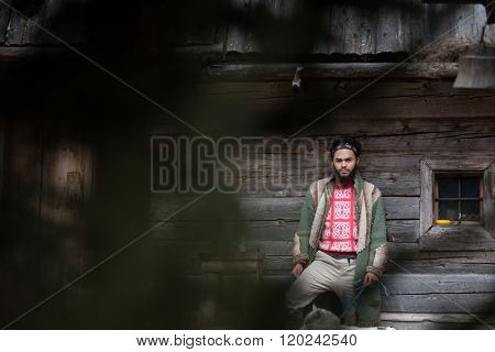 handsome young hipster man standing together with white husky dog in front of old vintage retro wooden house