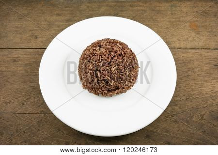 The cooked dark brown rice on the white plate on old wooden planks
