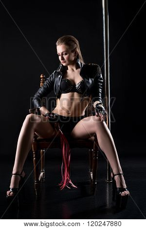 Sexy domineering woman with whip sits on chair