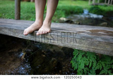 Kids feet standing on the wooden bridge in mountain creek