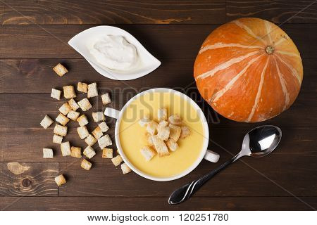 Cream Soup Of Pumpkin With Spices, With Cream, Crackers, On A Brown Wooden Table