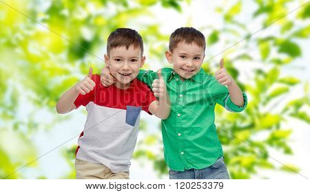 childhood, gesture, friendship, summer and people concept - happy smiling little boys showing thumbs up over green natural background