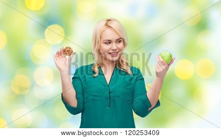 healthy eating, junk food, diet and choice people concept - smiling woman choosing between apple and cookie over green lights background