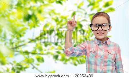 childhood, environment, education, ecology and people concept - happy little girl in eyeglasses pointing finger up over green natural background