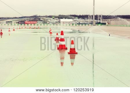 racing, motosports, extreme and motoring concept - traffic cones and sprinklers on wet speedway of stadium