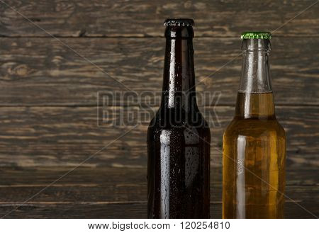 Two Sweating, Cold Bottle Of Beer On Dark Wooden Background