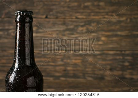 Sweating, Cold Bottle Of Beer Closeup On Dark Wooden Background