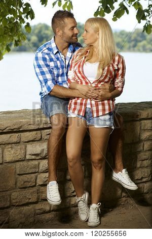 Happy romantic couple embracing at riverside, looking at each other, outdoor, full length, shorts, sport shoe.