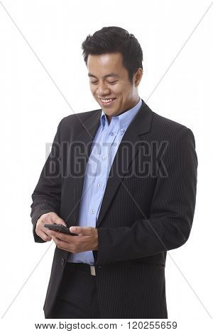 Young smiling Asian businessman dialing on mobilephone.