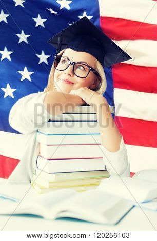 happy student in graduation cap with stack of books over american flag